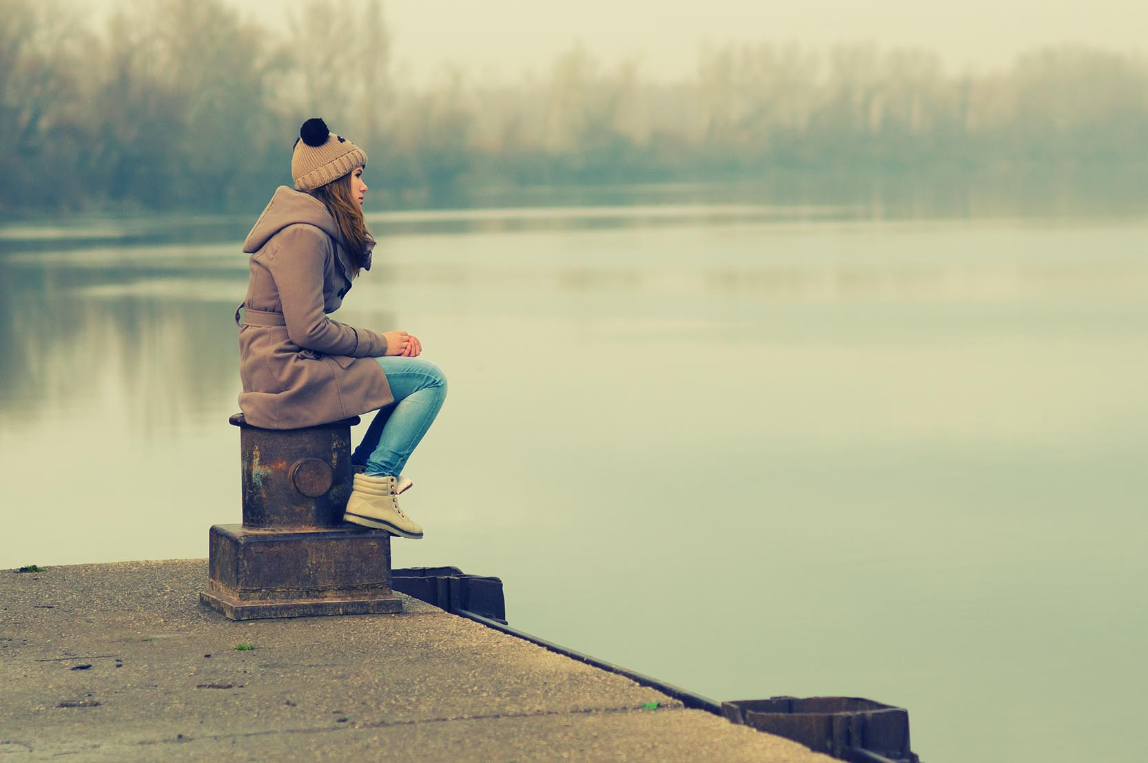 image of Lonely teenage girl sitting on the dock